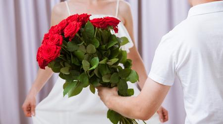 bouquet fleurs: Homme donnant à roses jeune femme, gros plan tir