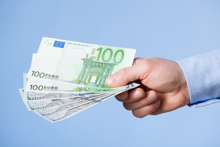 hand reaching: Businessmans hand reaching out euro banknotes, blue background