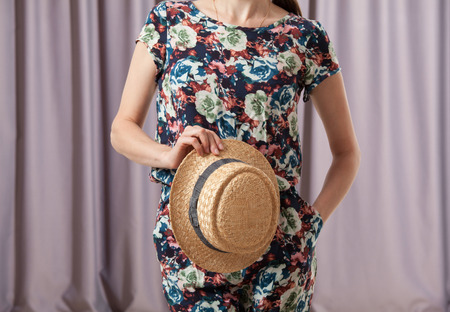 unrecognizable: Unrecognizable young woman holding a straw hat Stock Photo