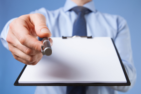 proposing: Businessman holding a clipboard with empty sheet of paper and proposing a pen, blue background