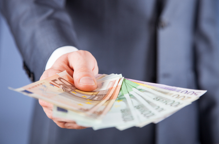 reaching out: Businessmans hand reaching out euro banknotes, blue background