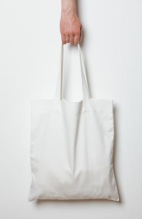 textile: Male hand holding white textile bag, neutral background Stock Photo