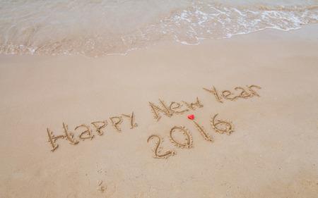 Happy New Year  drawn on sand on a sunny beach, closeup shot