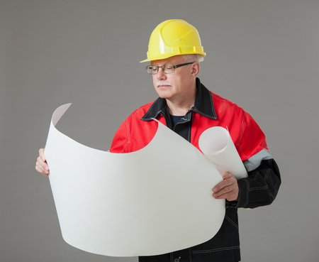examining: Builder examining a new project, gray background Stock Photo