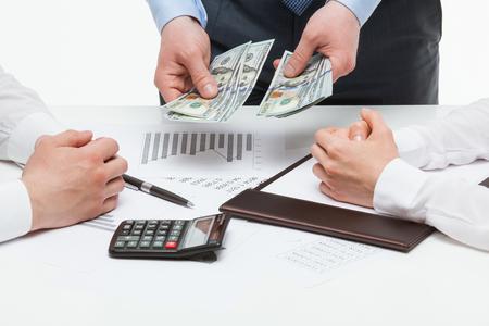 collaborators: Boss allocating money among collaborators, white background Stock Photo
