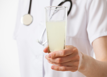 dilute: Doctor holding a glass with drug , white background