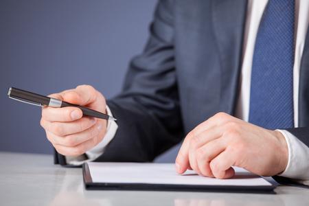 businessman signing documents: Businessman signing documents, blue background Stock Photo