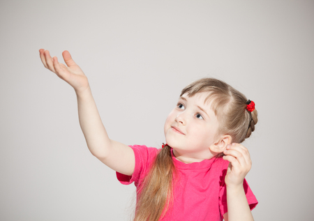 Happy little girl reaching out her palm and catching something, neutral background photo