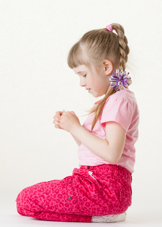 Pretty little girl holding and examining something, white background photo
