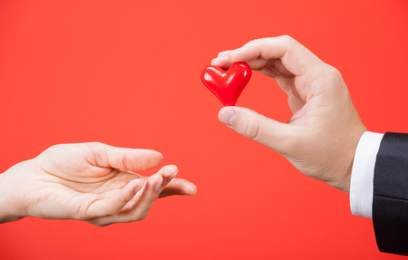 ceramic heart: Young man giving a ceramic heart to woman, red background