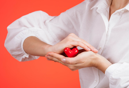 ceramic heart: Female hand holding a ceramic heart on red background Stock Photo