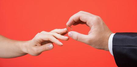 mariage: Proposition du mariage: l'homme de mettre la bague de fiançailles sur un doigt de sa petite amie; gros plan de mains