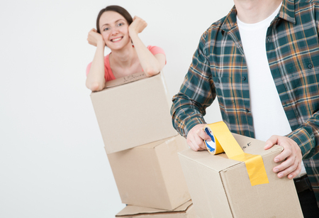 'young things': Young couple packing their things in cardboard boxes, neutral background