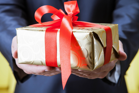 felicitation: Male hands holding a gift - closeup shot Stock Photo