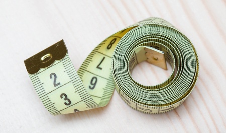 centimetre: Yellow tape measure on wooden background