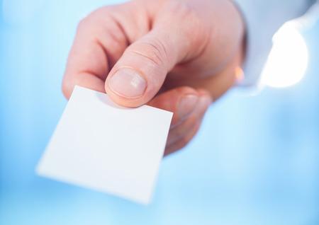 reaching out: Mans hand reaching out a business card - closeup shot
