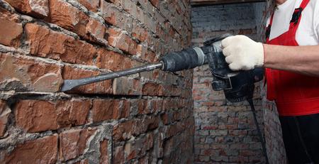 albañil: Constructor en uniforme y casco rojo trabaja con un plugger contra la pared de ladrillo