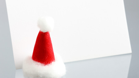 neutral background: Clear New Year card with Santas cap on neutral background with reflection
