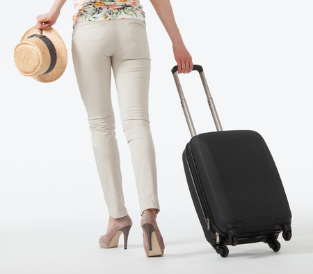 go to: Young woman  with suitcase going away, white background, full length portrait