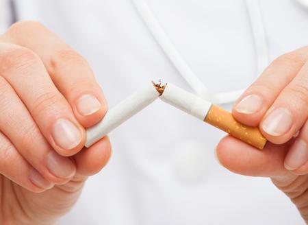 las manos del médico la celebración de un cigarrillo roto, concepto de estilo de vida saludable Foto de archivo