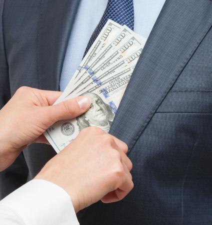 venality: Giving a bribe into a pocket - closeup shot Stock Photo