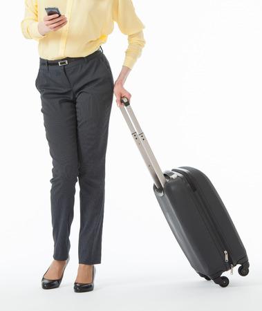 Vrij jonge vrouw die een mobiele telefoon en een koffer, witte achtergrond houdt