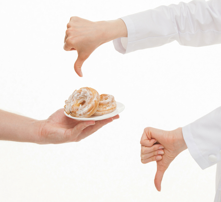 censure: Nutritionist condemning unhealthy eating and showing a sign of thumb down, white background