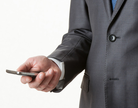 solid background: Unrecognizable businessman holding a cellphone, white background Stock Photo