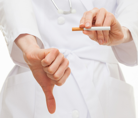deleterious: Doctors hands showing disabling gesture and holding a cigarette, healthy lifestyle concept
