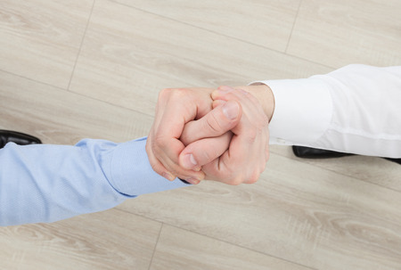 assent: Businessmens hands demonstrating a gesture of a strife or solidarity, view from above Stock Photo