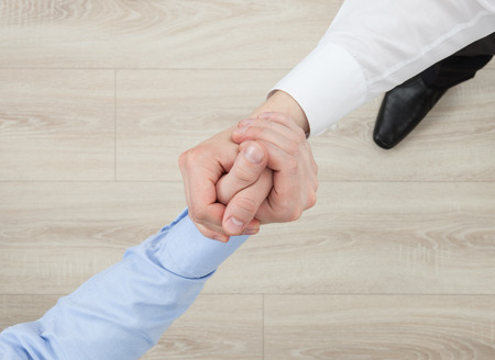 strife: Businessmens hands demonstrating a gesture of a strife or solidarity, view from above Stock Photo