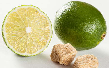 unrefined: Ripe limes and pieces of unrefined cane sugar, neutral background