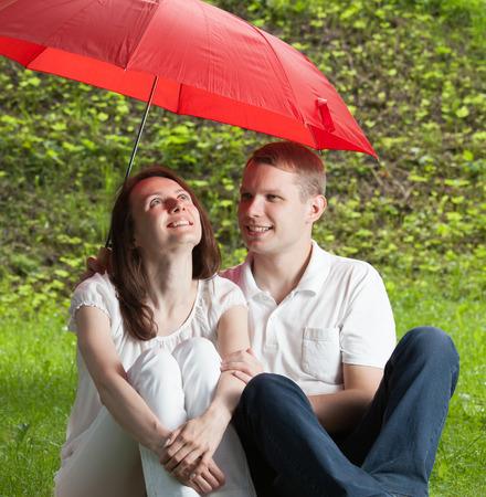 sotto la pioggia: Coppia in amore, seduta sul prato verde estate sotto l'ombrello rosso