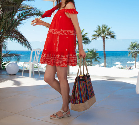sundress: Happy young woman in a red sundress holding  a bag and an umbrella on seafront background