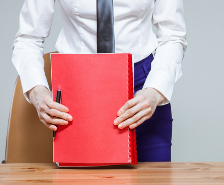 neutral background: Unrecognizable young businesswoman on workplace with folders, neutral background