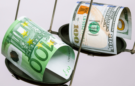 haggling: Dollars and euros banknotes on the scale, neutral background Stock Photo