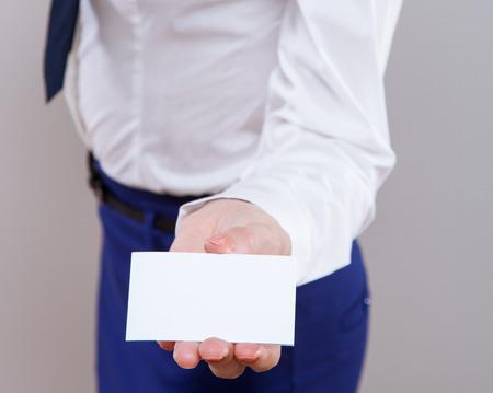 neutral background: Businesswoman in wormalwear showing business card, neutral background Stock Photo