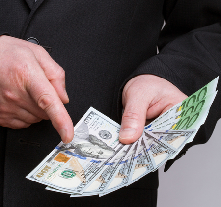 haggling: Unrecognizable businessman holding dollars and euro and choosing dollars