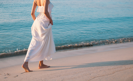 sundress: Happy young woman in a white sundress walking by the beach