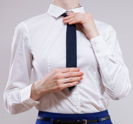 Unrecognizable businesswoman sets the necktie on neutral background Stock Photo