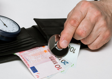 put pressure: Male hands put a stethoscope to cash-box with euro money - closeup shot