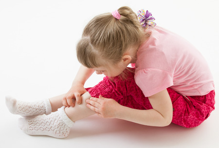 attentively: Little girl scrutinizing her leg attentively on the floor