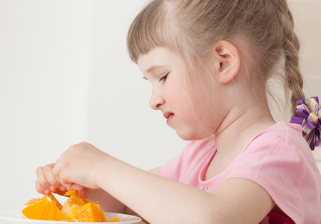 reluctance: Pretty little girl dont want to eat an orange