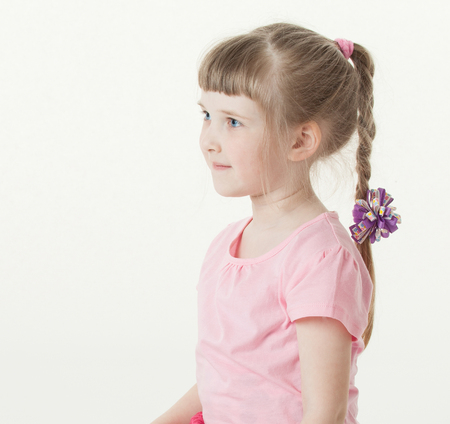 upgrowth: Portrait of a pretty little girl sitting on the floor, white background