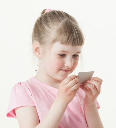 intrest: Pretty little girl reading the text on a card, white background