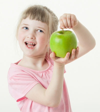 upgrowth: Happy little girl showing a green apple, white background Stock Photo
