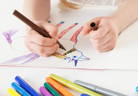 upgrowth: Unrecognizable little girl drawing a narwhal - closeup shot Stock Photo