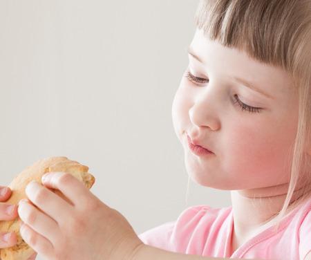 enjoyment: Pretty little girl eating a doughnut with enjoyment Stock Photo