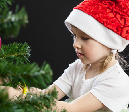 sincere girl: Beautiful little girl decorates the Christmas tree, black background Stock Photo