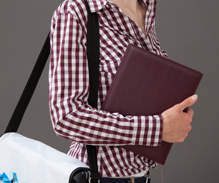 upgrowth: Portrait of a young woman holding a book and a briefcase, gray background